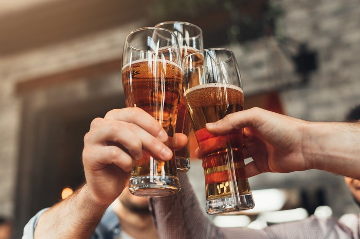 Three friends clink their glasses of beer.