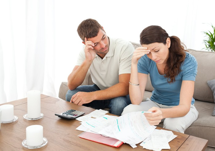 Man and woman with worried expressions looking at documents on table.