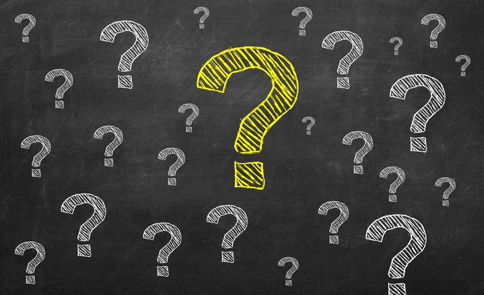 Several question marks drawn on a chalkboard, with a giant yellow question mark in the middle