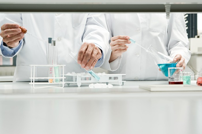 Research scientists' hands use pipettes, test tubes, and beakers.