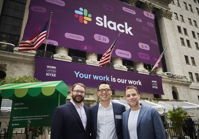 Slack CTO Cal Henderson, CFO Allen Shim, andCEO Stewart Butterfield in front of the New York Stock Exchange with a banner announcing the company's IPO.