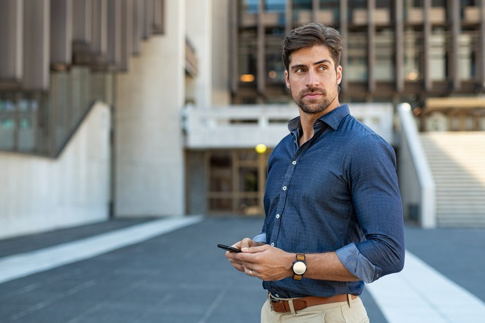 Man standing outdoors holding cell phone