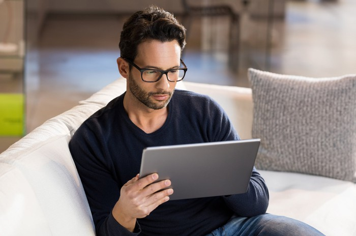 Man with serious expression holding tablet