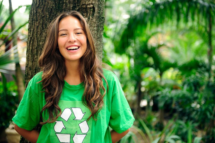 Smiling young woman wearing green t-shirt with recycle symbol.