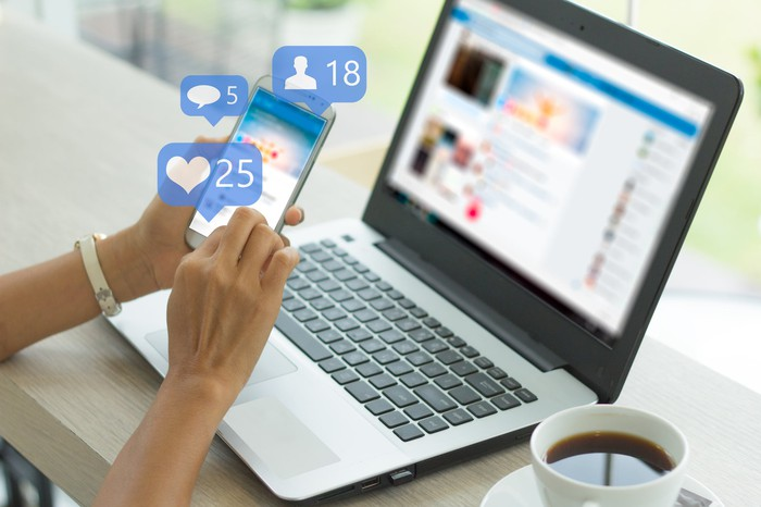 A woman uses a social networking app on a phone and a laptop.