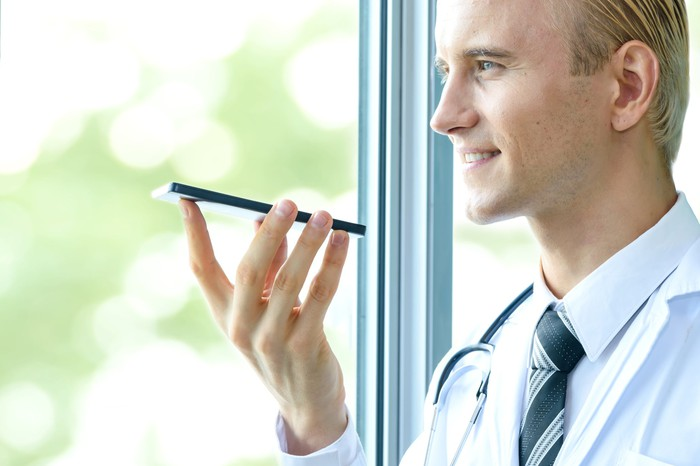 A doctor holding a mobile phone.
