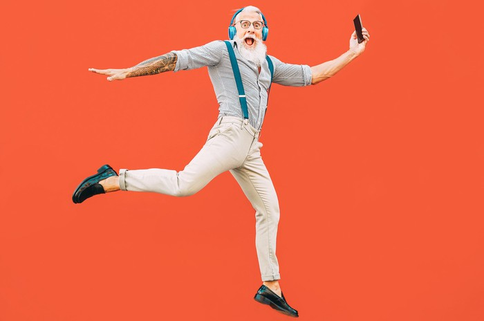 An oder man with a beard in suspenders leaps while wearing headphones and holding a cell phone.