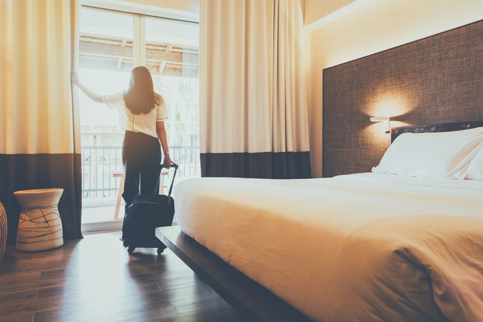 Woman holding luggage standing near sliding door in hotel room