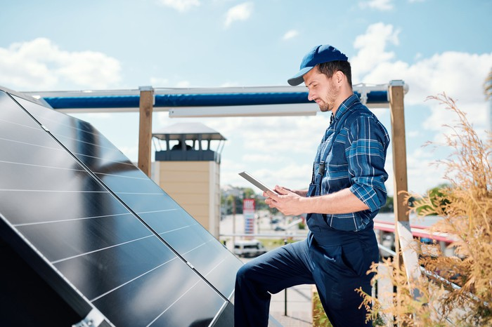 Standing beside solar panels, a man works on a tablet.