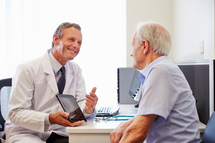 A physician holding up a tablet and showing it to a senior patient