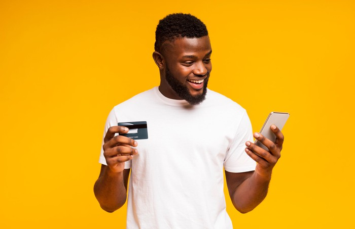 A happy young man holds a phone in one hand and a credit card in the other.