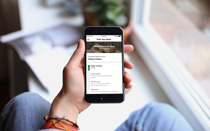 Hand holding phone with Grubhub app displayed.