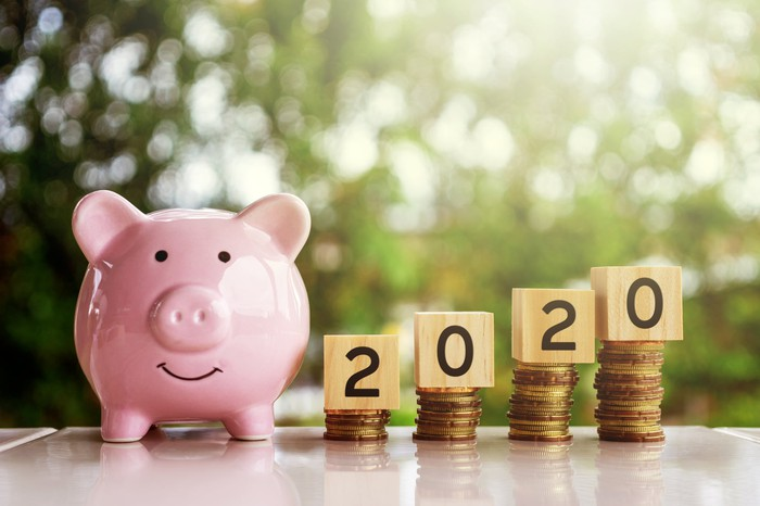 """A piggy bank next to stacks of coins a blocks spelling out """"2020""""."""