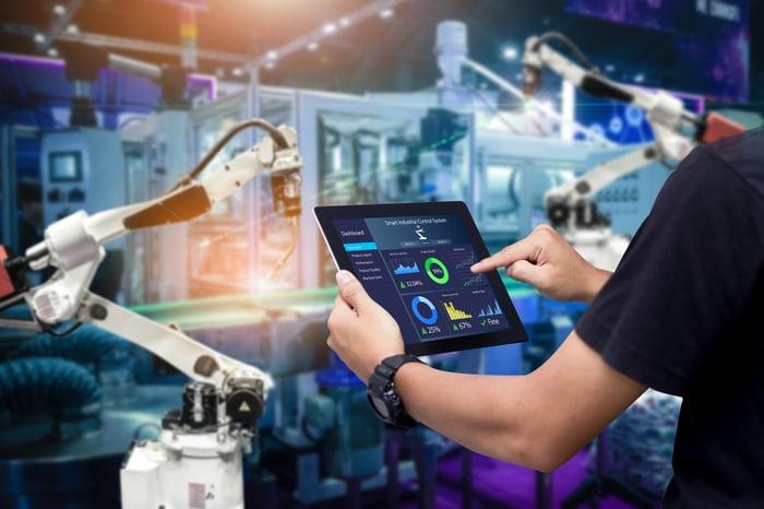 A man digitally monitoring production robots.