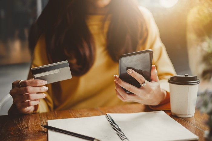 Woman with a credit card in one hand and a smart phone in the other making an online e-commerce purchase.