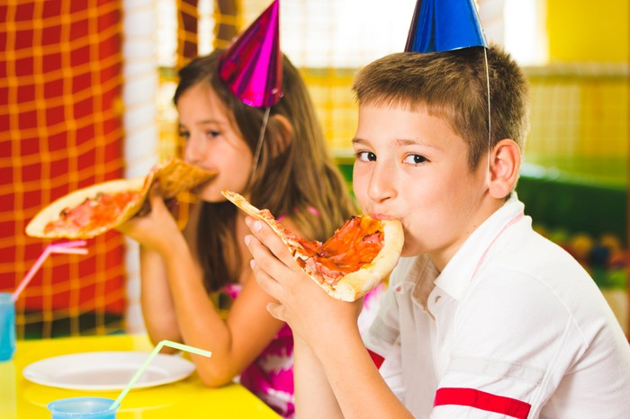 two kids at a birthday pizza party eating pizza