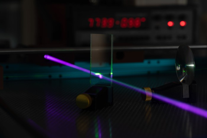 A purple laser beam fired through a prism in a laboratory experiment.