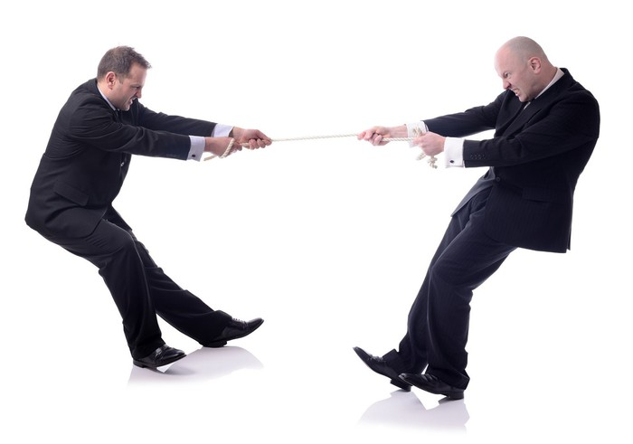 Two men playing tug of war.