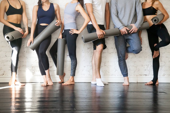A group of men and women standing against a wall dressed in athletic wear and carrying mats for a yoga class.