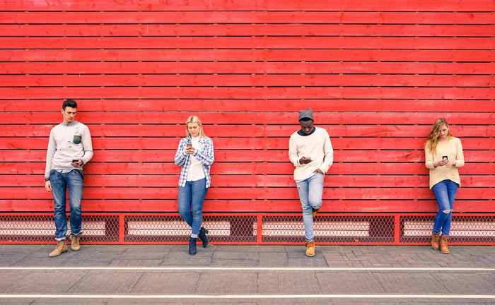 Four people use smartphones as they lean on a red wall.
