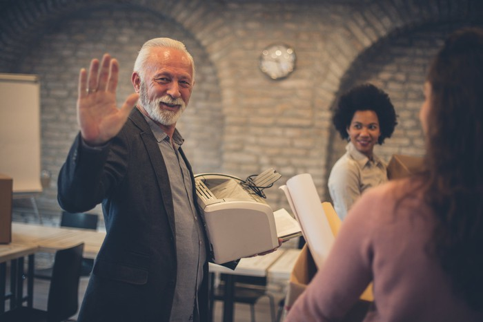 Smiling older man holding printer waves goodbye while two women look on