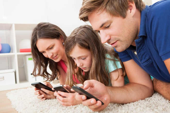 A mom, dad, and daughter sit together on the floor, each looking at their mobile phones.