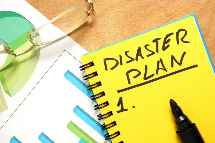 "A yellow notepad with the words ""disaster plan"" written on it rests on a table."