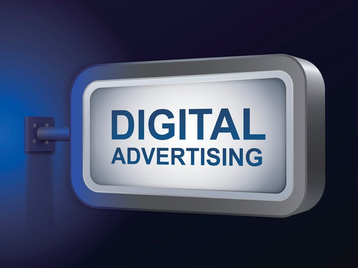 """A silver sign displaying the words """"digital advertising"""" protrudes from a wall."""