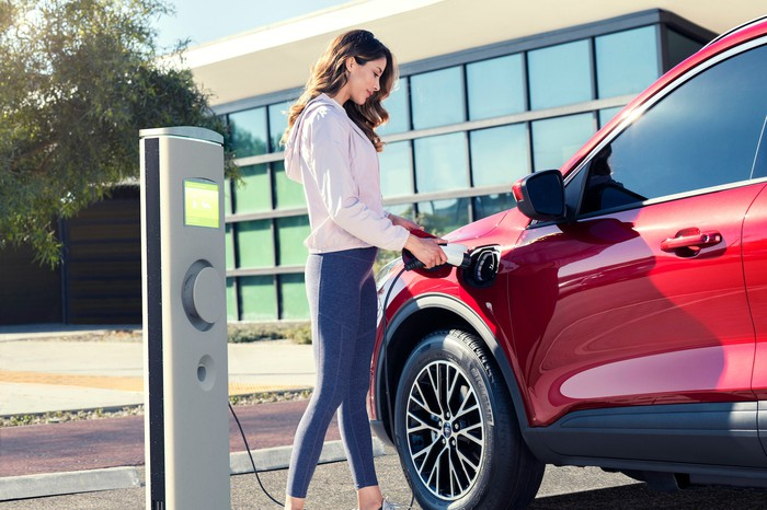 A woman plugs a charger into a red Ford Escape plug-in hybrid SUV.