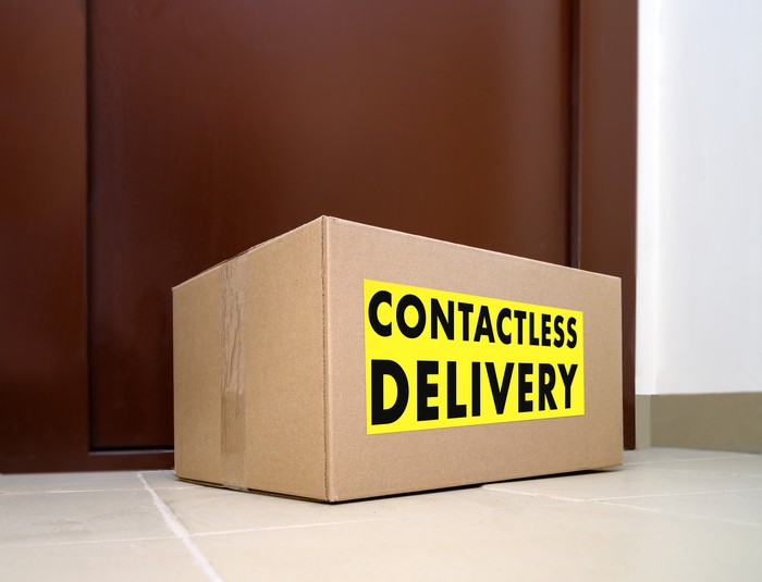 """A cardboard box with  a label that says """"contactless delivery"""" sits outside a front door."""