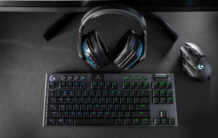 A gaming headset, mice, and keyboard sitting on a black table.