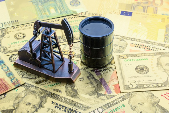 A miniature oil well and oil barrel stand on a pile of euro and dollar bills.