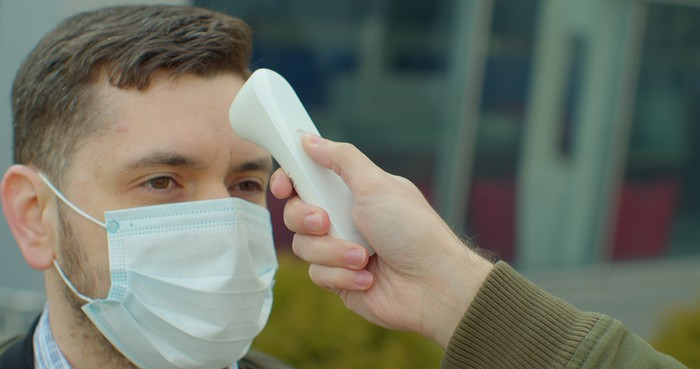 A person wearing a mask has his temperature checked.