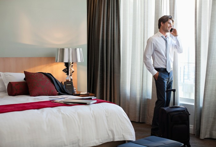A man in a suit talking on a cellphone near the window in a hotel room.