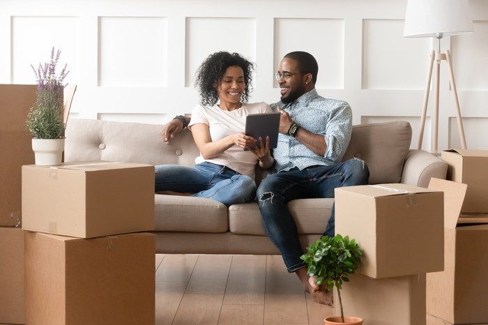 A couple sitting on a couch looking at real estate online with boxes around them.