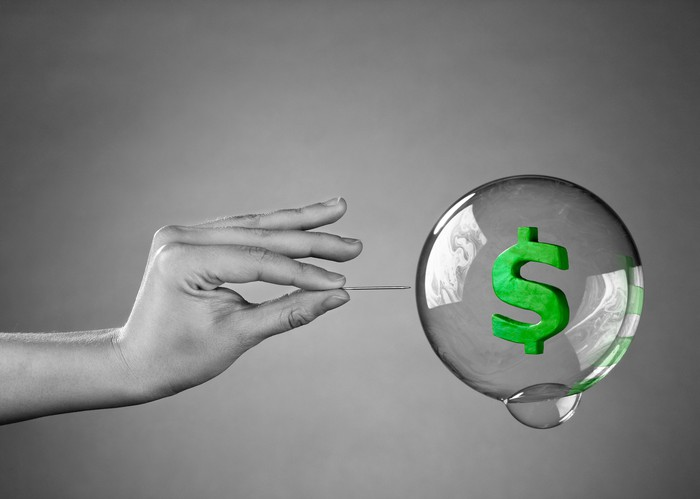 A grayscale hand holding a needle is poised to pop a bubble containing a green dollar sign.