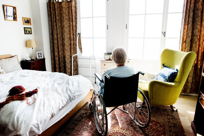 Woman in wheelchair in large bedroom