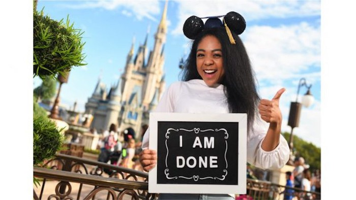 A graduate wearing a mouse-eared graduation cap holding an I am done sign in front of a Disney park castle.