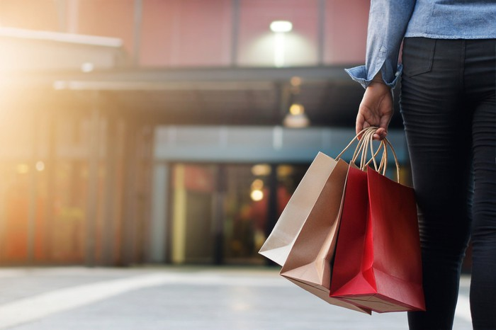 Shopper holding bags and heading towards mall entrance.