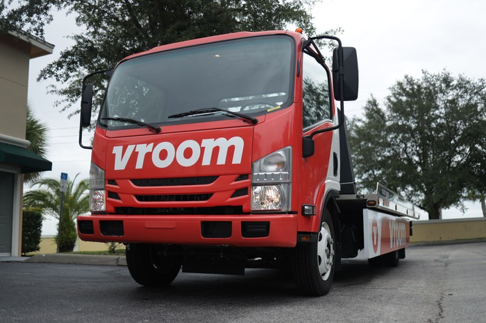 A Vroom transportation truck with an empty flatbed
