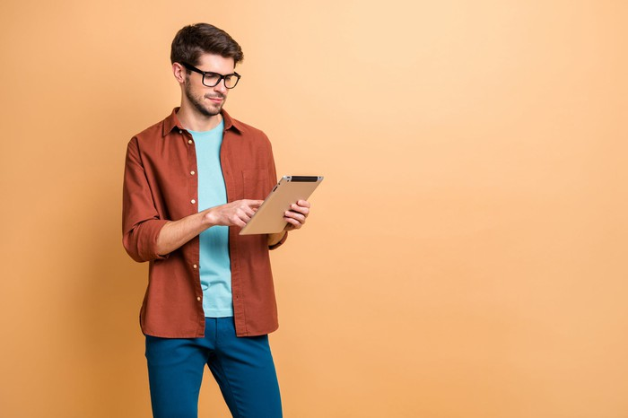 A young man in casual wear and glasses holds and works an electronic tablet.