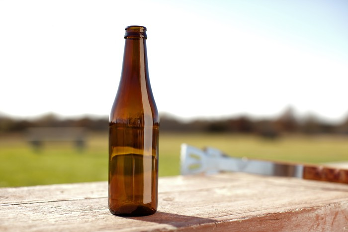 A single glass bottle sits on a table outside