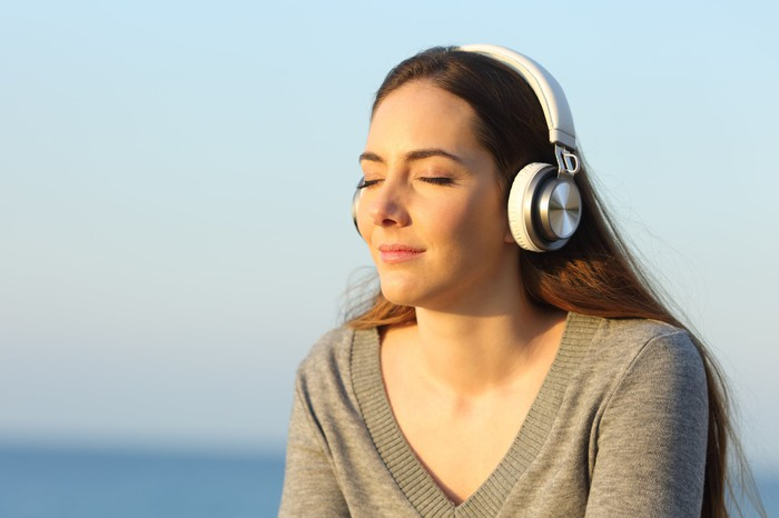 A woman listens to music on headphones.