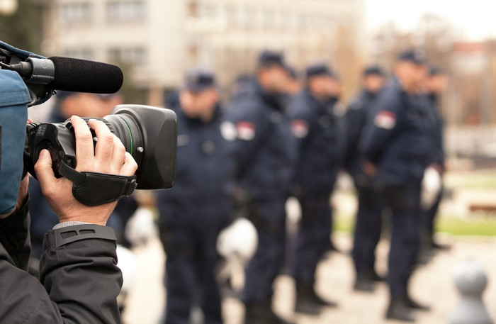 A cameraman filming a group of police officers.