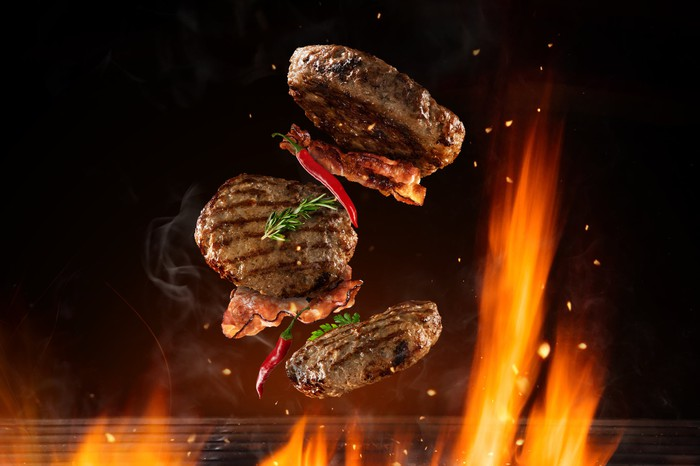 gourmet burgers with peppers flipping above grilling flames
