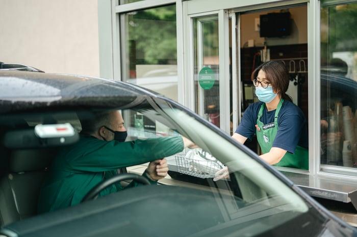Starbucks worker serving a customer in drive-thru.