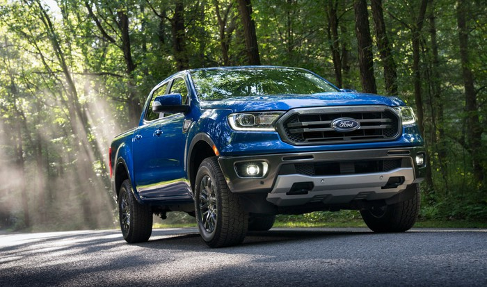 A blue 2020 Ford Ranger, a midsize pickup truck, on a wooded road.