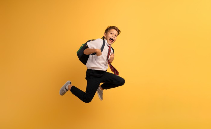 A smiling young child jumping on a bright yellow background.
