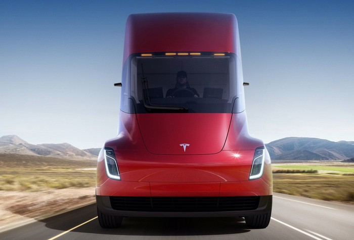Red semi tractor trailer truck with Tesla logo on a road with semi-arid hills in background.