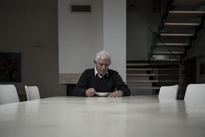 Sad old man sitting at table in gray room.